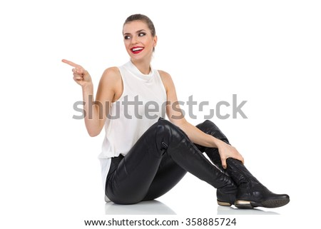 Happy young woman in white shirt, black leather trousers and boots sitting on a floor, pointing and looking away. Full length studio shot isolated on white - stock photo