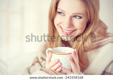 happy young woman is basking  under a blanket and a cup of coffee on a winter morning at home - stock photo