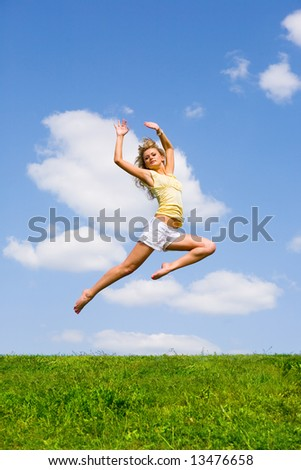 Happy young woman is dancing in a field