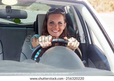 Happy young woman is driving a car - stock photo