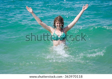 Happy young woman is enjoying in spray of turquoise sea.