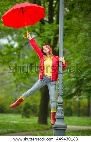 Happy young woman is having fun on the rain. She climbed the outdoor lamp post in the park, and smiling, dancing and singing.