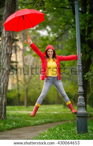 Happy young woman is having fun on the rain. She climbed the outdoor lamp post in the park, smiling and looking at camera.