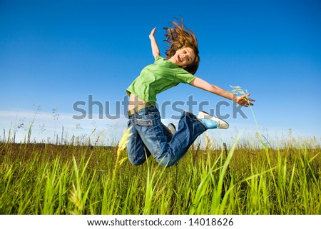 Happy young woman is jumping in a field - stock photo