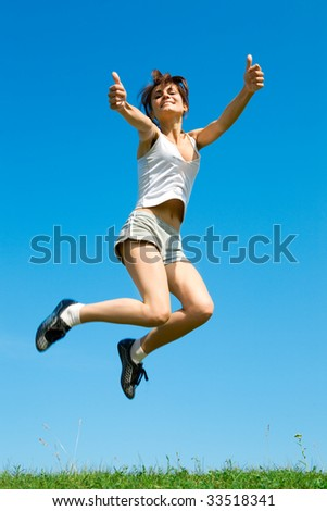 happy young woman is jumping on green grass under sky
