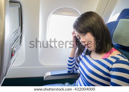 Happy young woman is sitting in the airplane, feel headache, asian