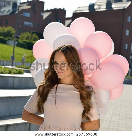 Happy young woman is whirling in park over city background and holding air balloons - stock photo