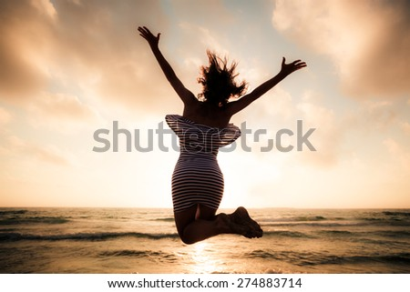 Happy young woman jumping at the beach. Summer vacation concept - stock photo