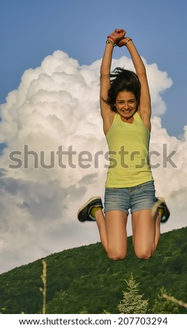 Happy young woman jumping high in the mountains  - stock photo