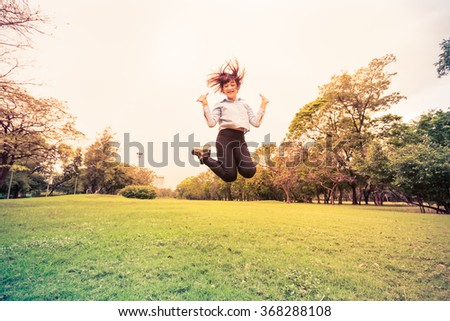Happy young woman jumping high on the park - stock photo