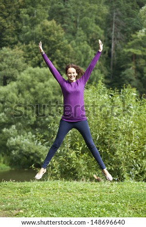 Happy young woman jumping in summer day