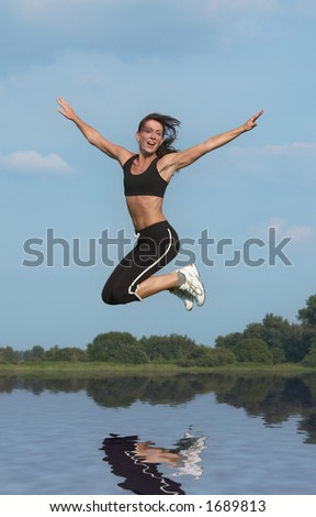 happy young woman  jumping on a sunny day above water