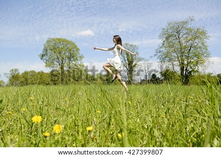 happy young woman jumping on flower meadow