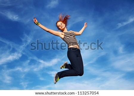 Happy young woman jumping on open air - stock photo