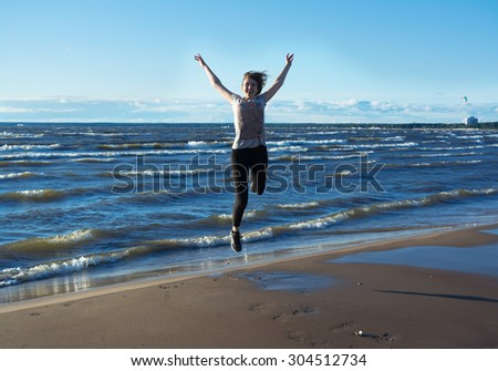 Happy young woman jumping on the beach. She feels freedom and happiness. - stock photo