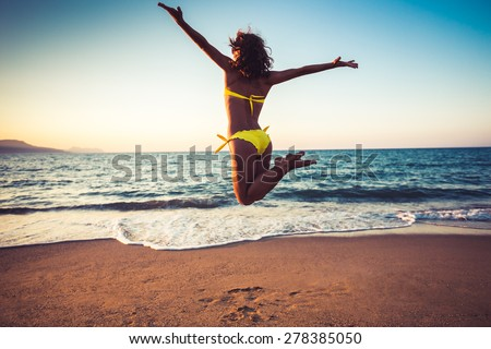 Happy young woman jumping on the beach. Summer vacation and freedom concept - stock photo