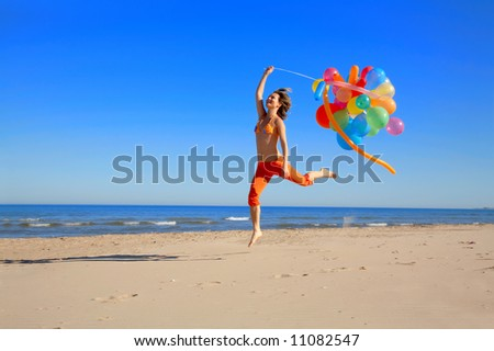 happy young woman jumping on the beach with different colored balloons