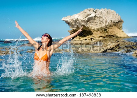 Happy young woman jumps in water against awesome rocky beach. Shot in De Hoop Nature Reserve, Western Cape, South Africa. - stock photo