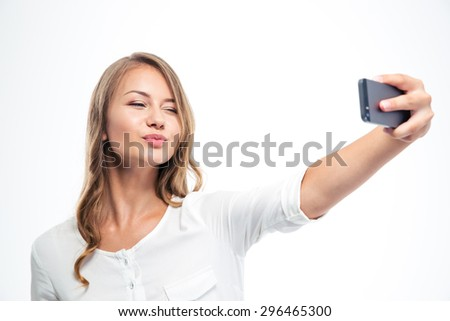 Happy young woman kissing and winking while making selfie photo on smartphone isolated on a white background  - stock photo