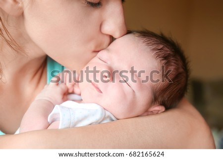 Happy young woman kissing her newborn baby boy, closeup