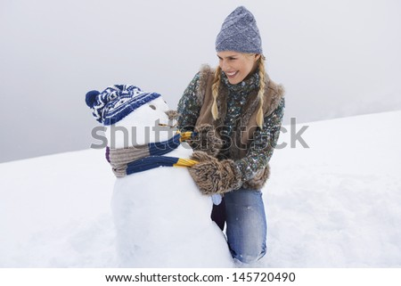 Happy young woman kneeling and dressing snowman on snow covered hill - stock photo