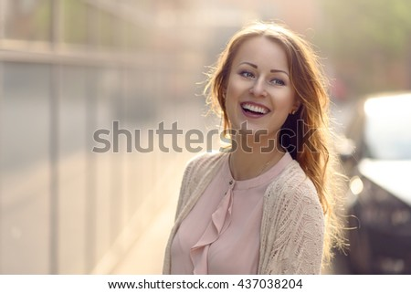 Happy young woman laughing towards the camera in early morning sunlight outdoors with copy space tho the left - stock photo