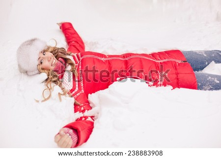 Happy young woman laying in snow - stock photo