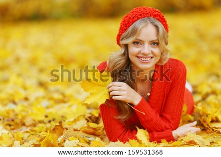 Happy young woman laying on autumn leaves in park