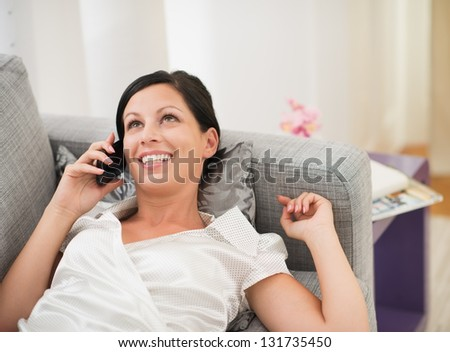 Happy young woman laying on couch and talking mobile phone - stock photo
