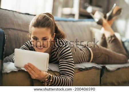 Happy young woman laying on couch and using tablet pc in loft apartment - stock photo