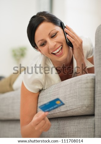 Happy young woman laying on sofa speaking mobile and looking on credit card - stock photo
