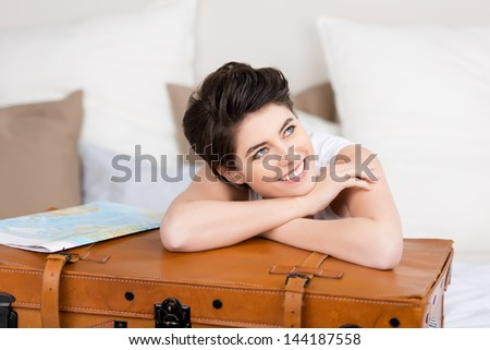 Happy young woman leaning on suitcase while looking away on bed - stock photo