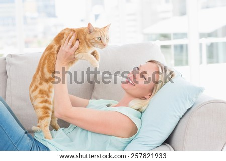 Happy young woman lifting cat on sofa at home
