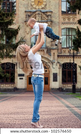 Happy young woman lifting her son high up outdoors - stock photo