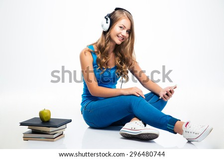 Happy young woman listening music in headphones on smartphone isolated on a white background. Looking at camera - stock photo