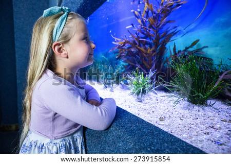 Happy young woman looking at fish in tank at the aquarium - stock photo