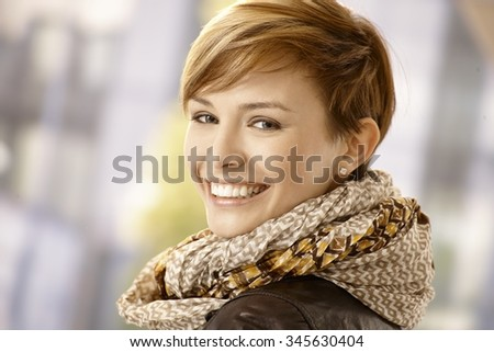 Happy young woman looking back and smiling - stock photo