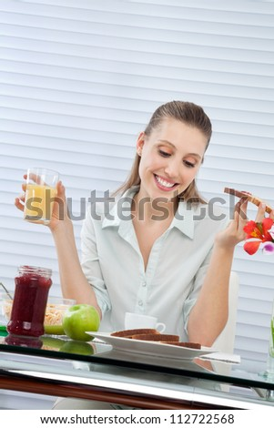 Happy young woman looking down at plate of bread slices while having orange juice
