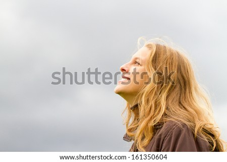 Happy young woman looking in to the sky - stock photo
