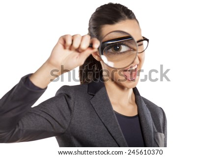 happy young woman looking through a magnifying glass
