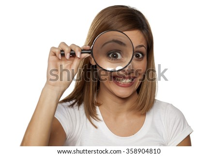 happy young woman looking through a magnifying glass - stock photo