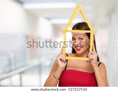 Happy Young Woman Looking Through House Frame, indoor - stock photo
