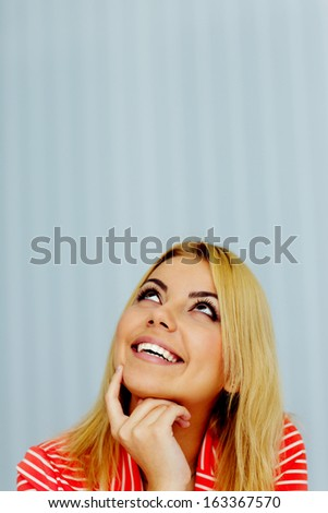 Happy young woman looking up at copyspace - stock photo