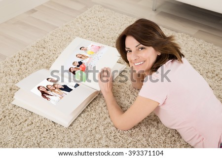 Happy Young Woman Lying On Carpet With Family Photo Album