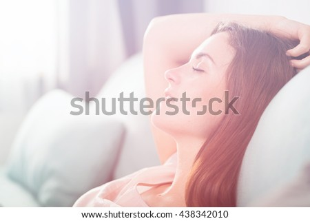 Happy young woman lying on couch and relaxing at home, casual style indoor shoot - stock photo