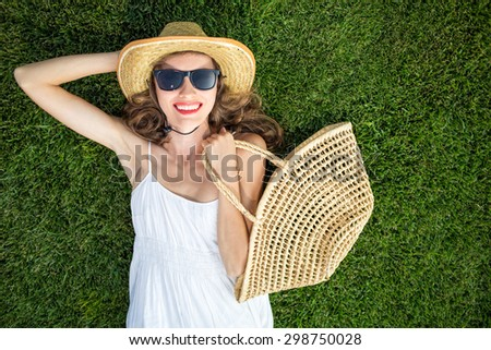Happy young woman lying on green grass laughing with excitement. copy space, view from above, copy space - stock photo