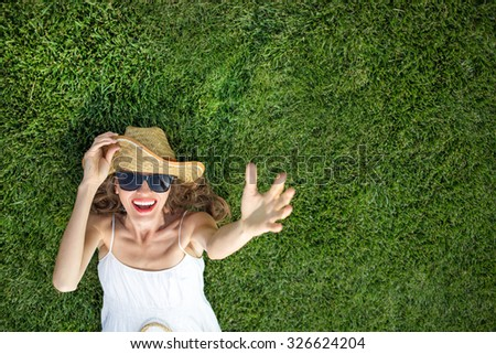 Happy young woman lying on green grass laughing with excitement. copy space, view from above, focus on face - stock photo