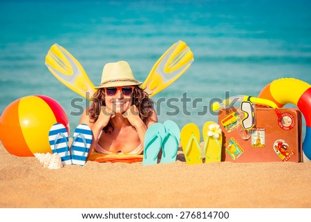 Happy young woman lying on the beach. Summer vacation concept - stock photo
