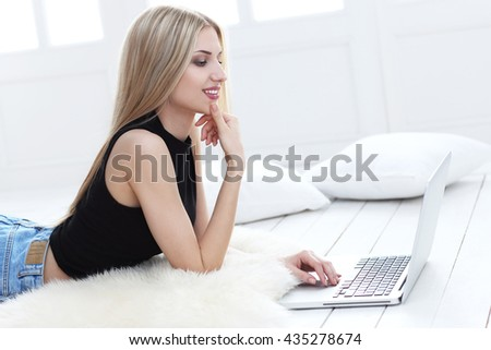 Happy young woman lying on the floor at home and using laptop