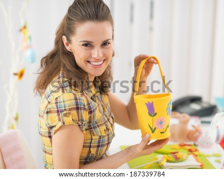 Happy young woman making easter basket - stock photo